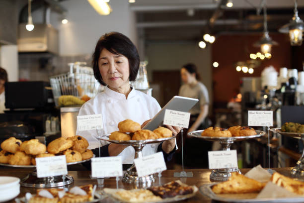 女店主經營這家咖啡館使用平板電腦 - 吧 公共飲食地方 個照片及圖片檔