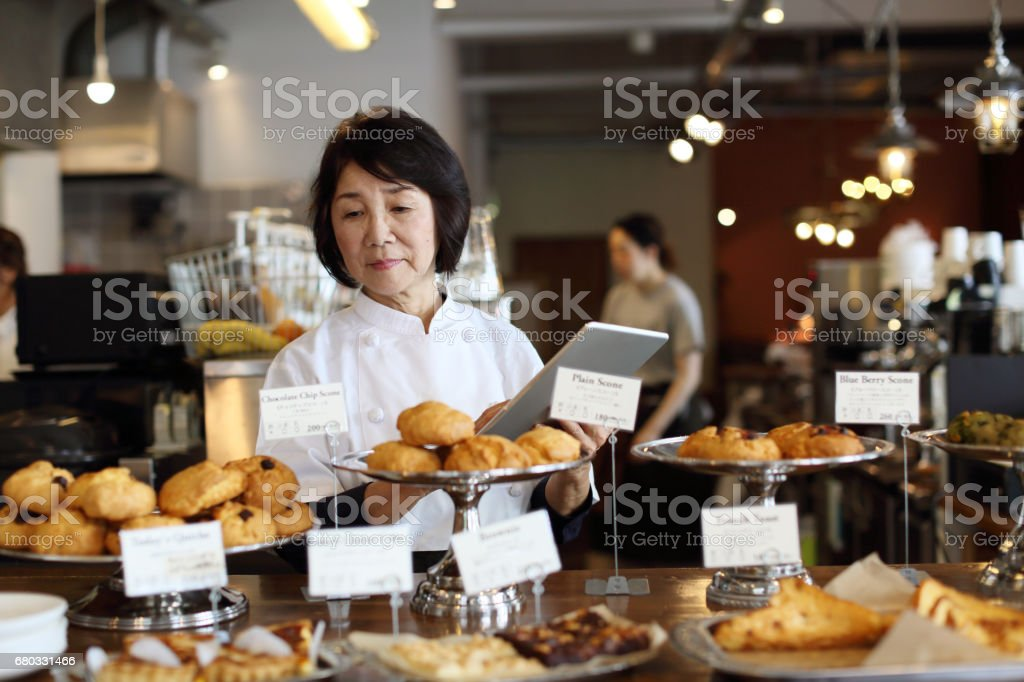 The woman storekeeper running the cafe uses a tablet stock photo