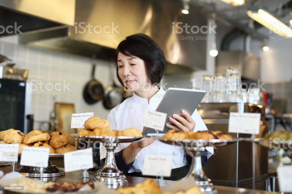 The woman storekeeper who manages the product with a tablet stock photo