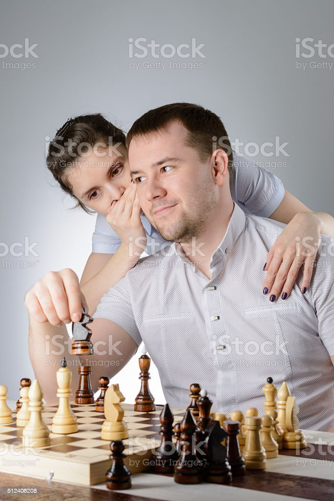 The woman tells the man's ear how to play chess stock photo