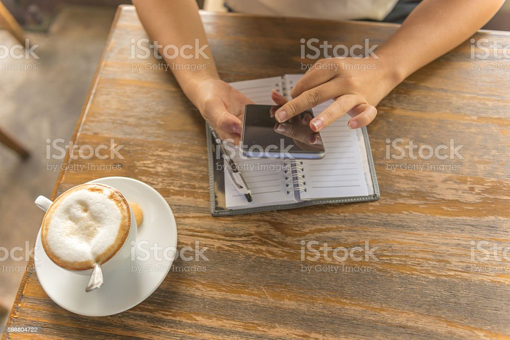 The woman using smartphone while having cappuccino stock photo