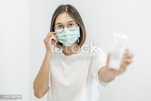 The woman wearing an Anamai mask shows a bottle of handwashing gel.