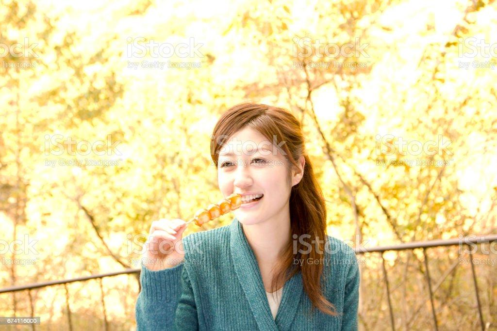 The woman who eats the Mitarashi dango royalty-free stock photo
