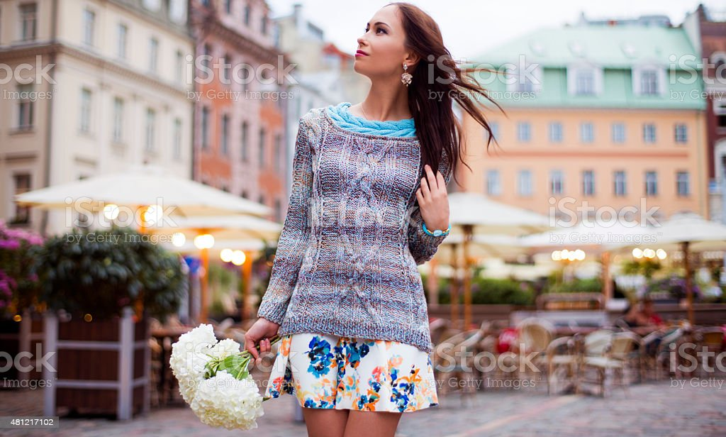 The woman with flowers, walks around the city stock photo