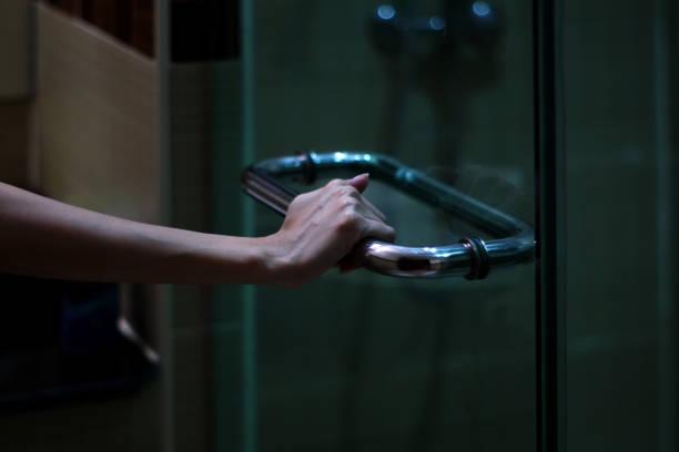 The woman's hand grabs handle door in the darkness. stock photo