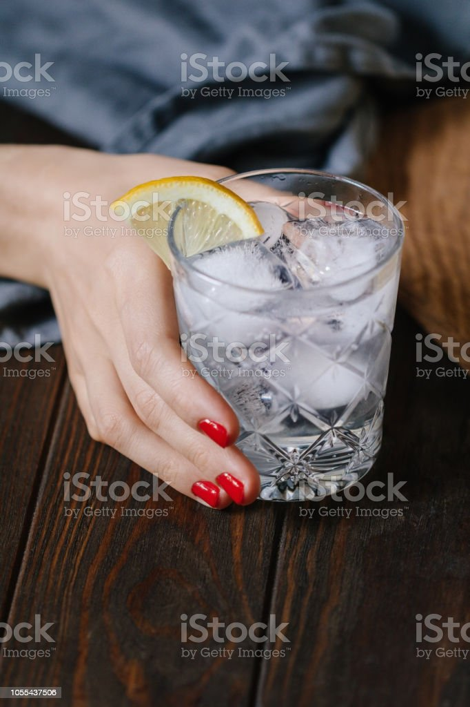 The woman's hand holds the cocktail with club soda, vodka, lemon and ice on a wooden table. Retro or vintage toned image. stock photo