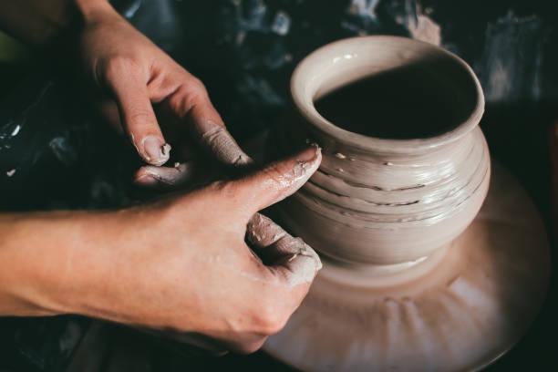 cerca de las manos de la mujer, el magistral estudio de la cerámica se trabaja con arcilla sobre un torno de alfarero - alfarería fotografías e imágenes de stock