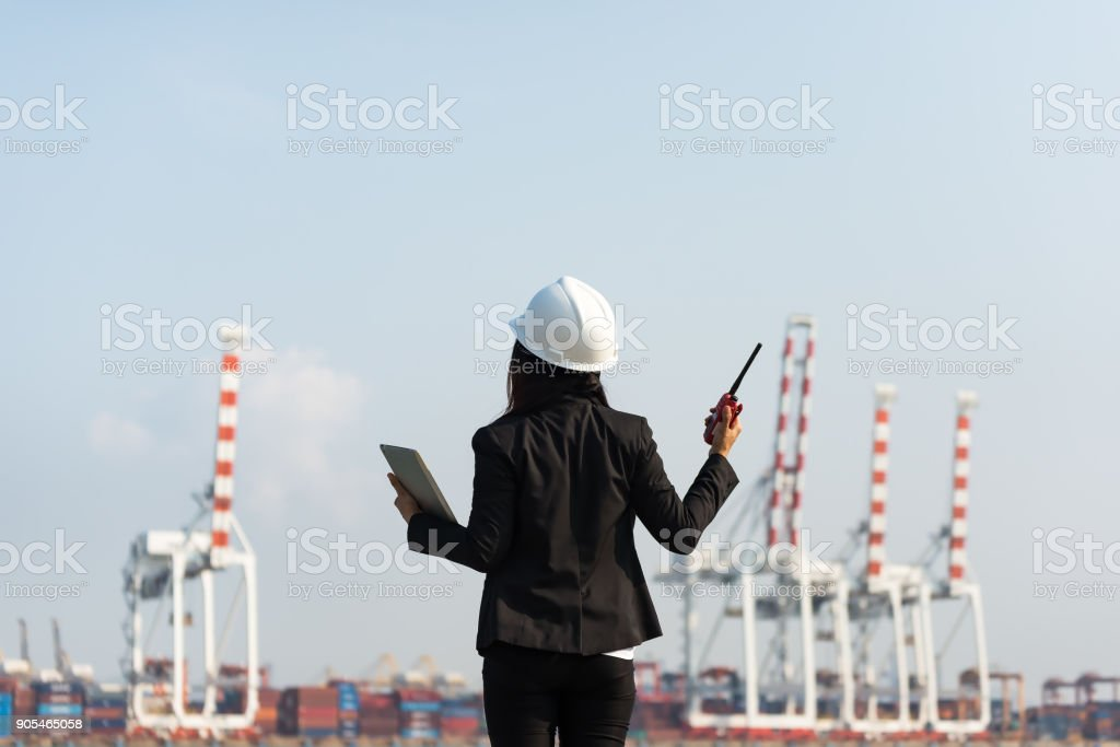 The women engineer working with container Cargo freight ship in shipyard at dusk for Logistic Import Export background stock photo