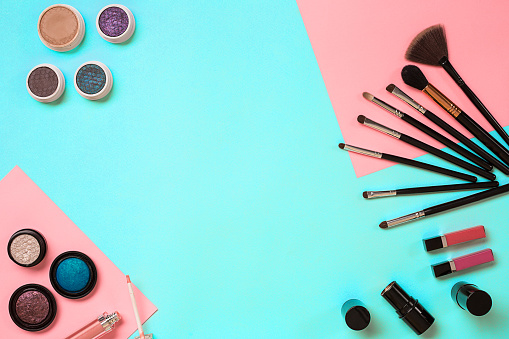 The women's cosmetics set on a blue background, modern woman. Brush for makeup, eye shadow, view from above. Copy space