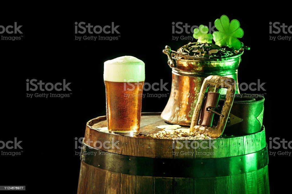 Le fond en bois avec beaucoup de pièces d'or et une grande tasse de bière avec un archet vert. photo libre de droits