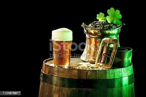 The wooden barrel background with lots of gold coins and a large mug of beer with a green bow. Background for St. Patrick's Day celebration