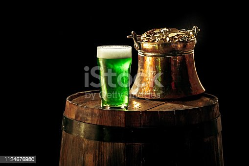 1124676977 istock photo The wooden background with lots of gold coins and a large mug of beer with a green bow. 1124676980