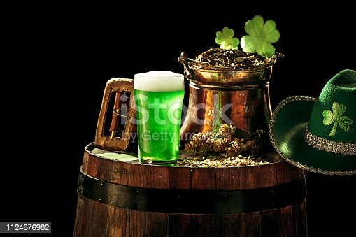 1124676977 istock photo The wooden background with lots of gold coins and a large mug of beer with a green bow. 1124676982