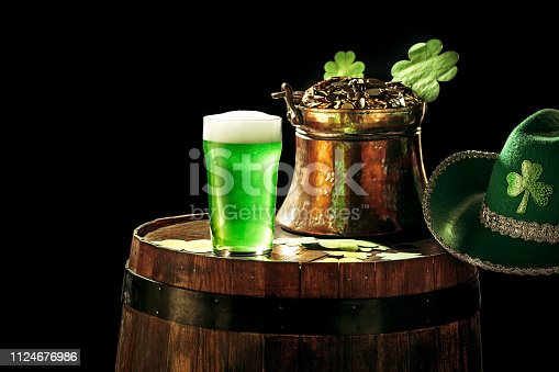 1124676977 istock photo The wooden background with lots of gold coins and a large mug of beer with a green bow. 1124676986