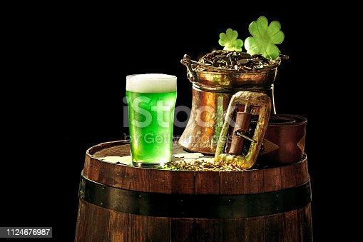 1124676977 istock photo The wooden background with lots of gold coins and a large mug of beer with a green bow. 1124676987