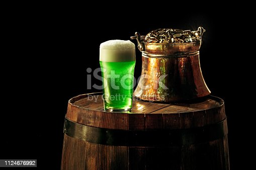 1124676977 istock photo The wooden background with lots of gold coins and a large mug of beer with a green bow. 1124676992