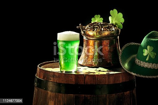 1124676977 istock photo The wooden background with lots of gold coins and a large mug of beer with a green bow. 1124677004