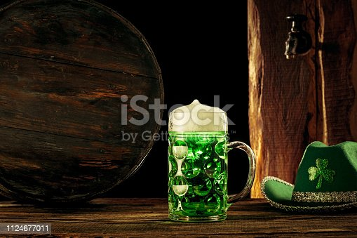 1124676977 istock photo The wooden background with lots of gold coins and a large mug of beer with a green bow. 1124677011