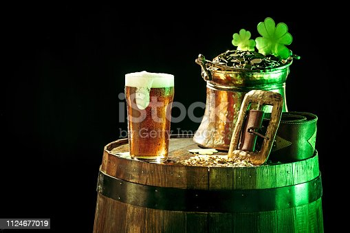 1124676977 istock photo The wooden background with lots of gold coins and a large mug of beer with a green bow. 1124677019