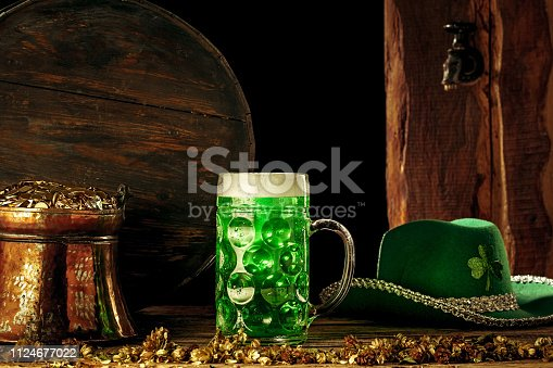 1124676977 istock photo The wooden background with lots of gold coins and a large mug of beer with a green bow. 1124677022