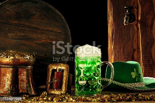 1124676977 istock photo The wooden background with lots of gold coins and a large mug of beer with a green bow. 1124677023