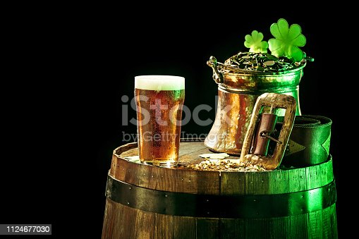 1124676977 istock photo The wooden background with lots of gold coins and a large mug of beer with a green bow. 1124677030