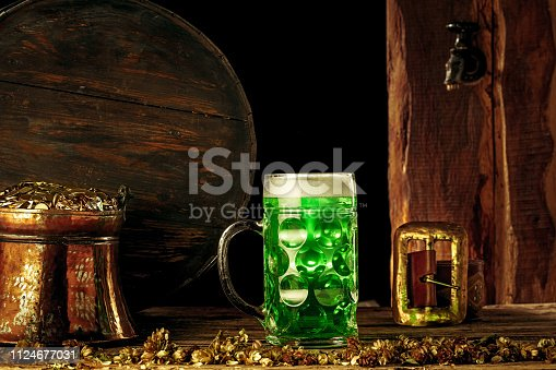 1124676977 istock photo The wooden background with lots of gold coins and a large mug of beer with a green bow. 1124677031