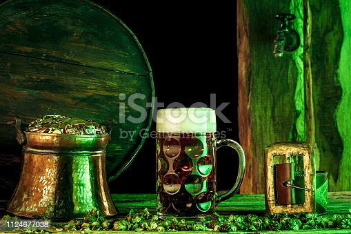 1124676977 istock photo The wooden background with lots of gold coins and a large mug of beer with a green bow. 1124677038