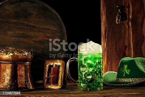 1124676977 istock photo The wooden background with lots of gold coins and a large mug of beer with a green bow. 1124677044