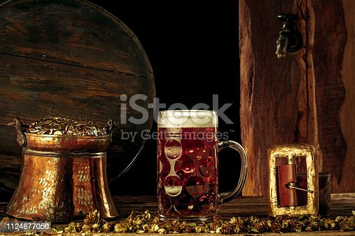 1124676977 istock photo The wooden background with lots of gold coins and a large mug of beer with a green bow. 1124677050