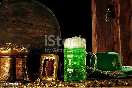 1124676977 istock photo The wooden background with lots of gold coins and a large mug of beer with a green bow. 1124677051