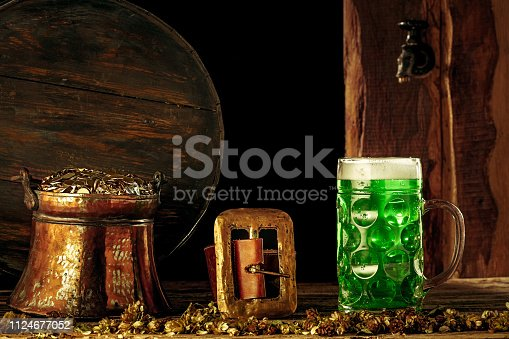1124676977 istock photo The wooden background with lots of gold coins and a large mug of beer with a green bow. 1124677052