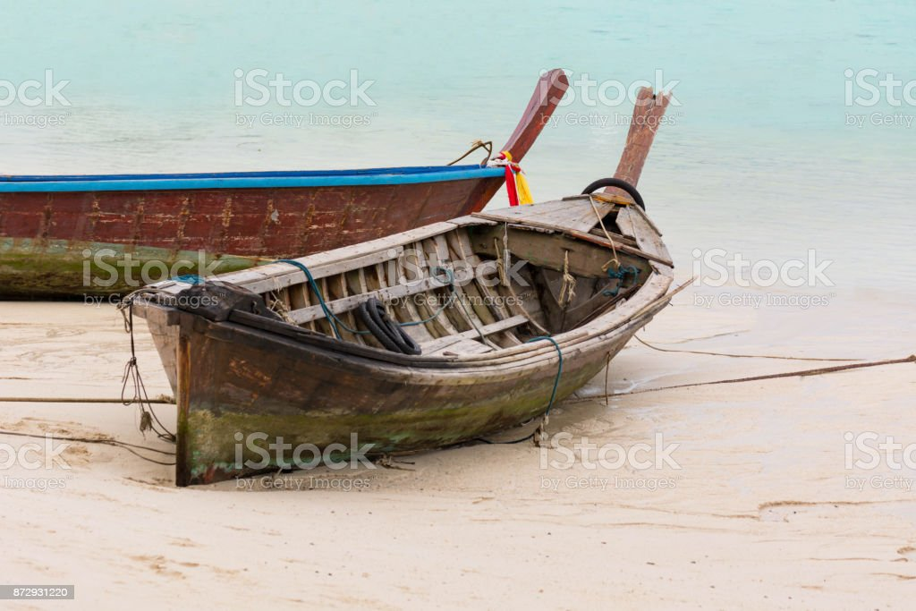 The Wooden Boat Collapsed On The Beach With Clear Blue Sea. stock photo