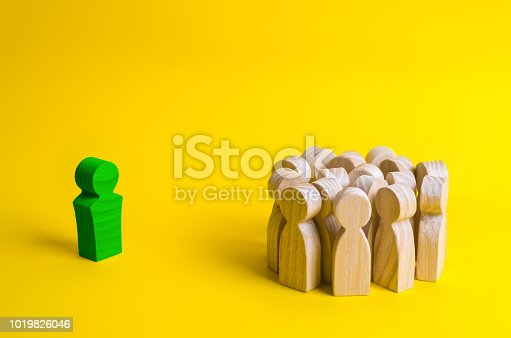 1007383644istockphoto The wooden figure of the leader stands near a crowd of people. Establishment of contact with workers and customers, leadership qualities. Successful integration into society and the collective. 1019826046