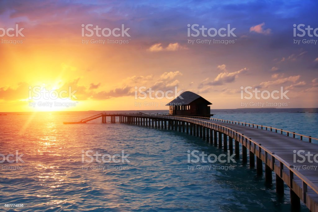 La route en bois au-dessus de la mer sur l'île tropicale. Coucher de soleil - Photo