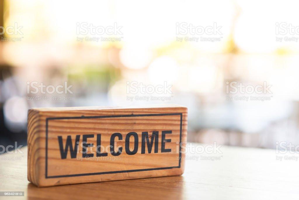 The wooden sign says welcome - Zbiór zdjęć royalty-free (Biznes)