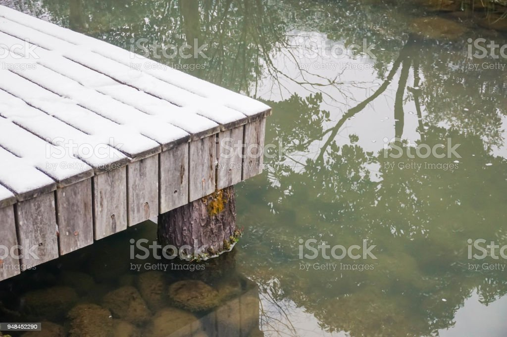 The wooden waterfront covered with snow nearby turbid lake stock photo