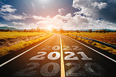 istock The word 2021 written on highway road in the middle of empty asphalt road 1283271579