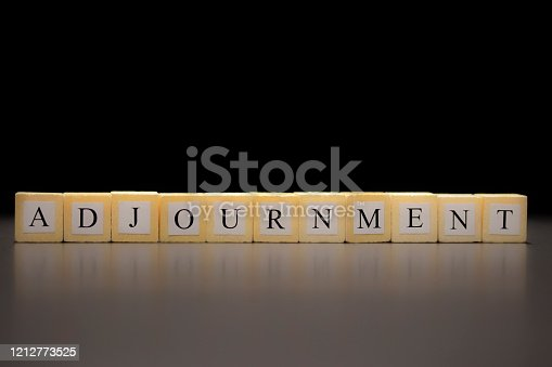 The word ADJOURNMENT written on wooden cubes, isolated on a black background...