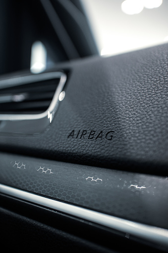 The word 'AIRBAG' embossed onto the dashboard of a modern car interior
