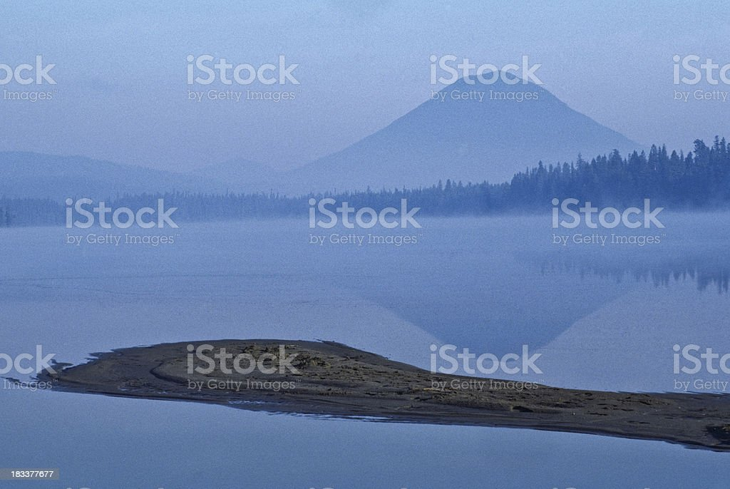 Foggy Sandspit and Mountain Reflected in the Lake stock photo