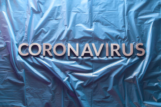 the word coronavirus laid with silver letters on crumpled blue plastic film - flat lay with centered composition the word coronavirus laid with silver letters on crumpled blue plastic film - centered flat lay composition with dramatic light decontamination stock pictures, royalty-free photos & images