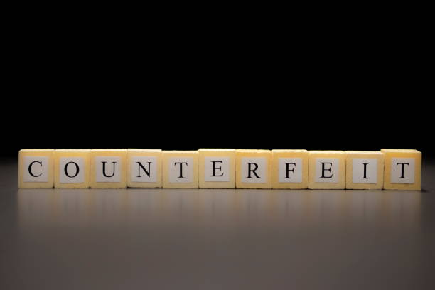 The word COUNTERFEIT written on wooden cubes isolated on a black background... The word COUNTERFEIT written on wooden cubes isolated on a black background... adulterate stock pictures, royalty-free photos & images
