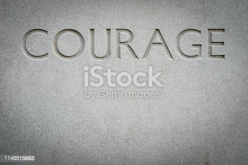 Conceptual Image Of The Word Courage Engraved Into Rock With Copy Space