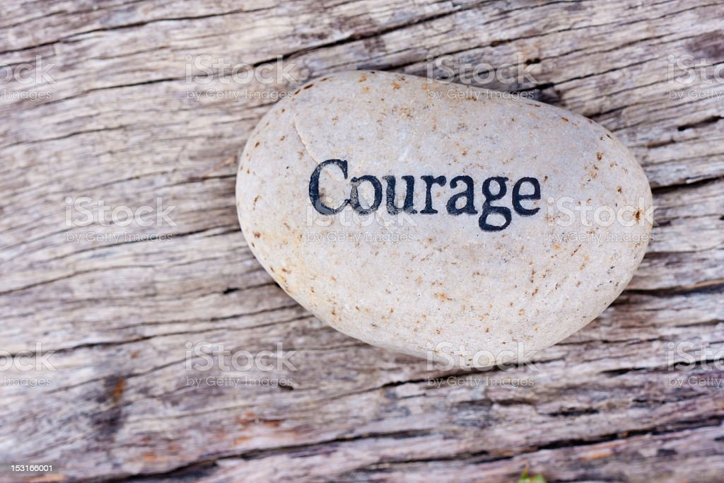 The word courage written on a smooth white rock on wood stock photo