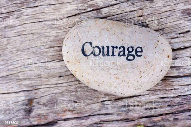 Photo of The word courage written on a smooth white rock on wood