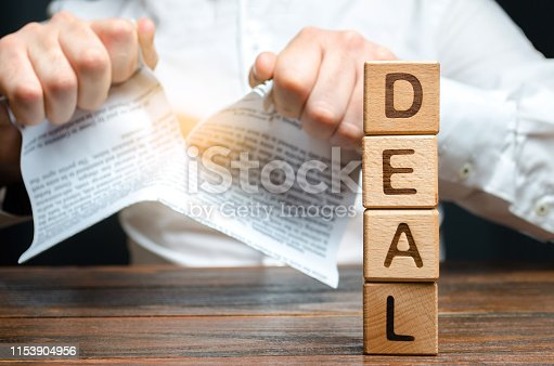 656916072 istock photo The word deal and businessman is breaking a contract in the background. Contract break unilaterally. Violation and default, conflict. Termination of employment, withdrawal from the agreement. 1153904956