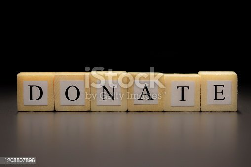 The word DONATE written on wooden cubes isolated on a black background...