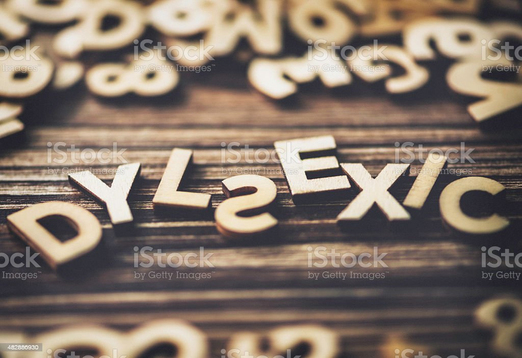 The word DYSLEXIC purposely mis-spelt out on a wood background stock photo
