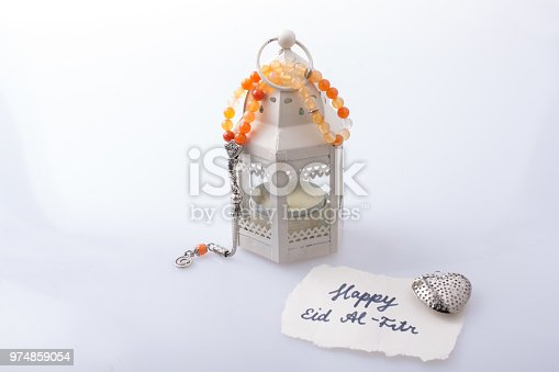istock the word EID EL FITR   on torn paper beside lantern and prying beads 974859054